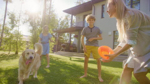 Beautiful Family of Four Play Catch Toy Ball with Happy Golden Retriever Dog on the Backyard Lawn. Idyllic Family Has Fun with Loyal Pedigree Dog Outdoors in Summer House Backyard.Handheld Dolly Shot Beautiful Family of Four Play Catch Toy Ball with Happy Golden Retriever Dog on the Backyard Lawn. Idyllic Family Has Fun with Loyal Pedigree Dog Outdoors in Summer House Backyard.Handheld Dolly Shot outdoors stock videos & royalty-free footage