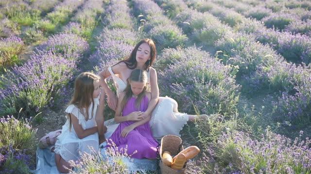 beautiful family of mother and her daughters on picnic on purple flower lavender field - wschodnio europejski filmów i materiałów b-roll