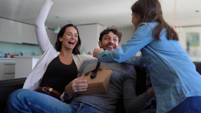 vídeos de stock, filmes e b-roll de pai surpreendente da família bonita com um presente emocionante para o dia de pai - fathers day