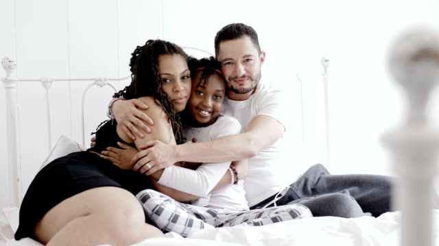 Beautiful family together bed at home Beautiful family embracing each other on bed at home transsexual stock videos & royalty-free footage