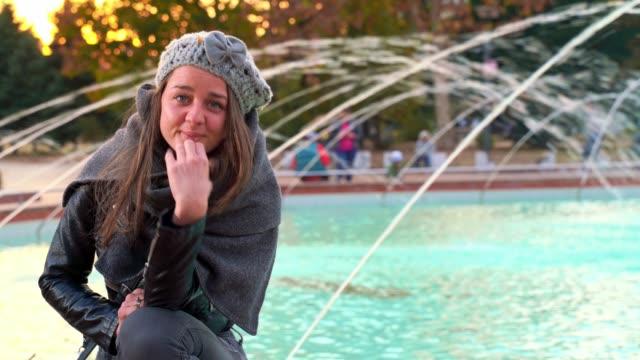 vackra fashionabla flicka sitter nära fountain tittar kameran blåsa kyssar - blåsa en kyss bildbanksvideor och videomaterial från bakom kulisserna