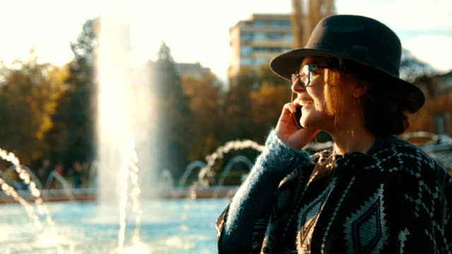 Beautiful fashionable girl standing in front of a running fountain and talking on the phone video