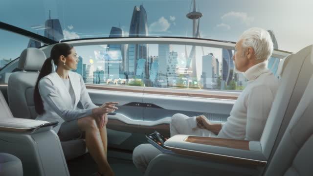 美しい女性とシニアの男性は、ドライバーレス自律走行車で会話をしています。未来的な自動運転バンは、ガラスの超高層ビルと近代的な都市の公道で移動しています。 - 自動化点の映像素材/bロール