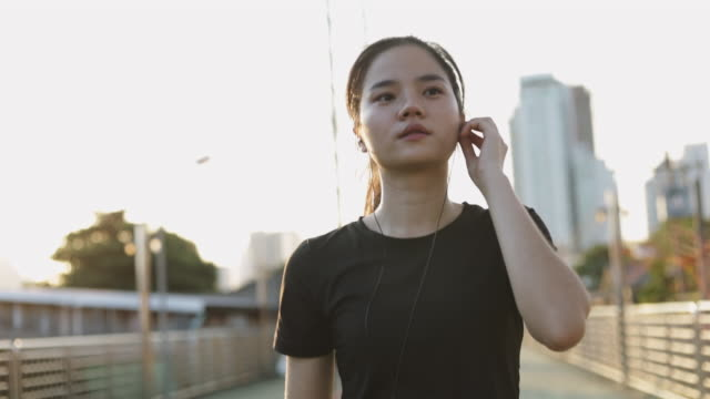 vídeos de stock e filmes b-roll de beautiful female athlete running wearing earphones using a smartphone listening to music while walking in the urban city sunset. jogging lifestyle healthy. - training