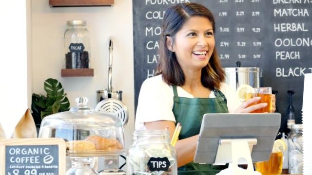 Hermosa mujer barista toma una mujer pedido en una tienda de café local - vídeo