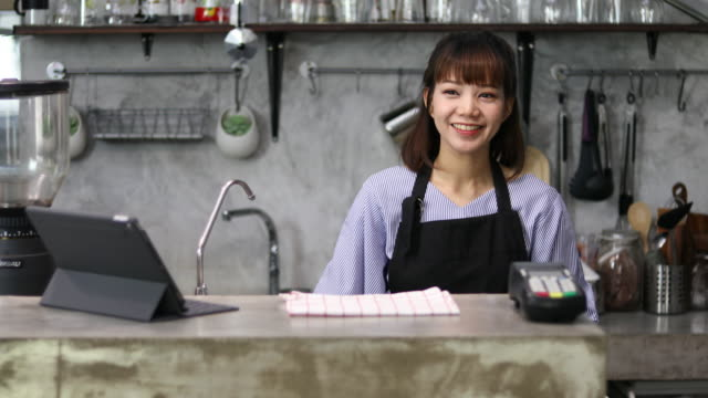 Beautiful female barista takes a female customer's order in a local coffee shop video