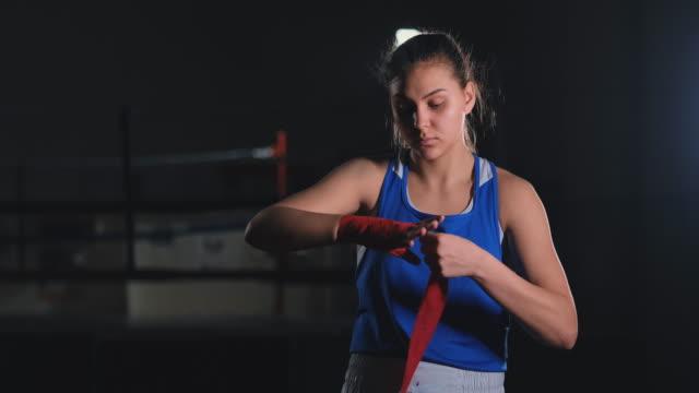 vídeos de stock e filmes b-roll de beautiful female boxer pulls red bandages around her arms. steadicam shot - campeão desportivo
