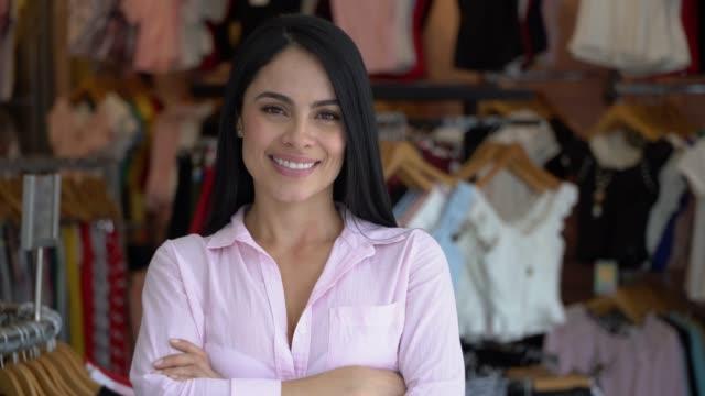 vídeos de stock, filmes e b-roll de linda fêmea empresário de uma loja de roupas, enfrentando câmera com braços cruzados sorrindo - boutique