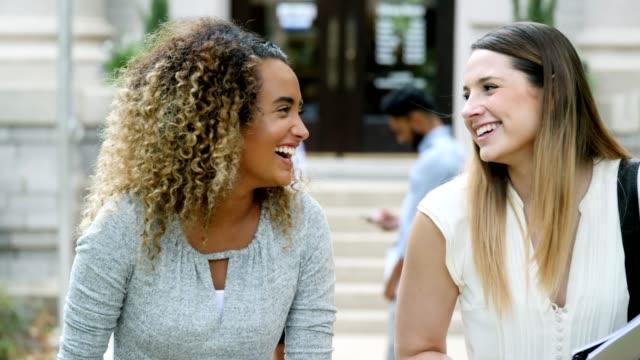 美しい女子大生がキャンパスに歩きながら笑う - 新学期点の映像素材/bロール