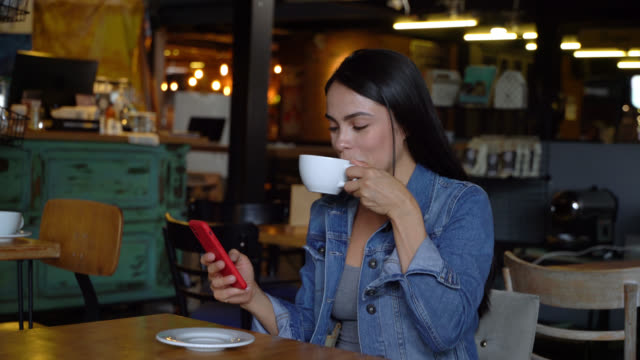 Beautiful female customer at a bakery enjoying a coffee and chatting on smartphone video