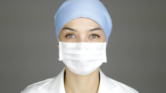 beautiful female doctor or nurse looking to the camera. she is ready for surgery. - face mask stock videos & royalty-free footage