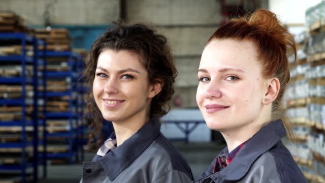 Beautiful female engineers smiling to the camera posing at the factory Close up portrait of two beautiful female factory workers or engineers smiling to the camera posing at the production plant. Manufacturing, women, feminism, profession, success. metal worker stock videos & royalty-free footage