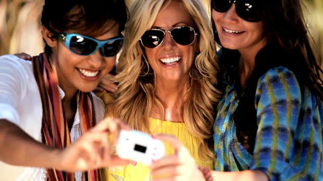 Beautiful female friends having fun using a camera video