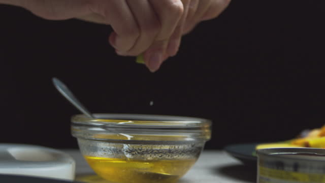 Beautiful female hands squeeze juice from lime or lemon.Woman prepares sauce for salad with honey and oil and juice