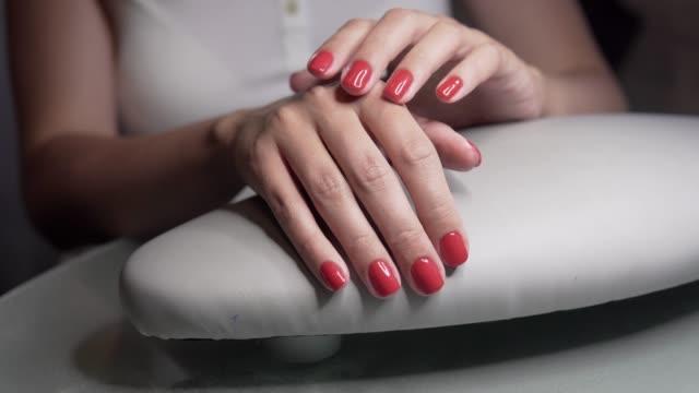 schöne weibliche hände mit roten nägeln in schönheit nagelstudio. schöne weibliche nägel und maniküre. - fingernagel stock-videos und b-roll-filmmaterial