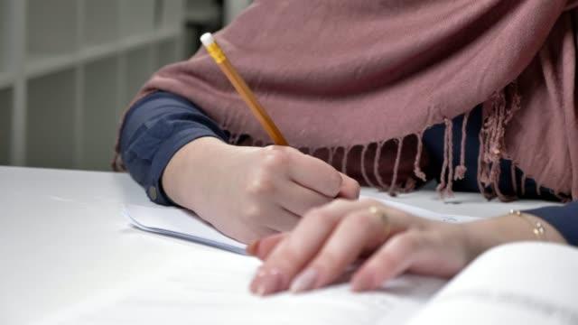 Beautiful female hands write in a notebook. Pencil. Manicure. Close-up. Arab women in the office 60 fps video
