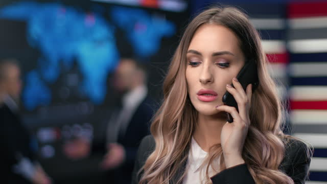 Beautiful female in suit white collar talking smartphone discussing job project at hi tech office