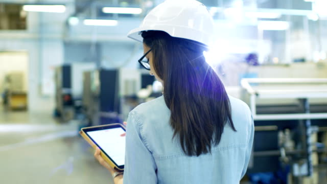 Beautiful Female Industrial Engineer in a Hard Hat Uses Tablet Computer while Walking in Big Factory. Beautiful Female Industrial Engineer in a Hard Hat Uses Tablet Computer while Walking in Big Factory. Shot on RED EPIC-W 8K Helium Cinema Camera. quality control stock videos & royalty-free footage
