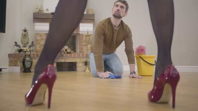 Beautiful female legs in elegant red high-heel shoes stomping on the foreground. Offended Caucasian man looking up at wife or girlfriend and starting washing the floor. Guilty husband or henpecked. Beautiful female legs in elegant red high-heel shoes stomping on the foreground. Offended Caucasian man looking up at wife or girlfriend and starting washing the floor. Guilty husband or henpecked. stamping feet stock videos & royalty-free footage