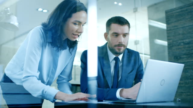 Beautiful Female Manager Gives Advice to a Businessman sitting at His Desk. They Do High-Five. Working on a Laptop in Modern Office.