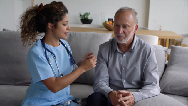 stockvideo's en b-roll-footage met mooie vrouwelijke verpleegkundige het controleren van een senior patiënt temperatuur met een digitale thermometer - thermometer