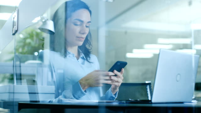 beautiful female office worker uses smartphone while sitting at her working desk with laptop on it. modern glass and concrete room. - sales video stock e b–roll