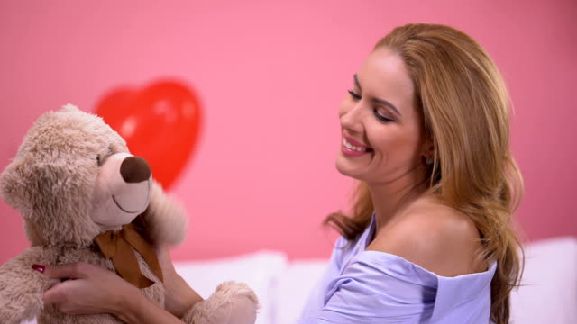 Beautiful female playing with teddy bear sitting in bedroom, precious gift, love