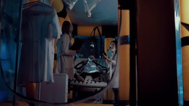 stockvideo's en b-roll-footage met mooie vrouwelijke wetenschappers voeren een wetenschappelijk experiment op een vreemdeling in het ruimtelaboratorium. geïnstalleerde schermen en apparatuur. zijdelingse overspanning van de camera. - ventilator bed