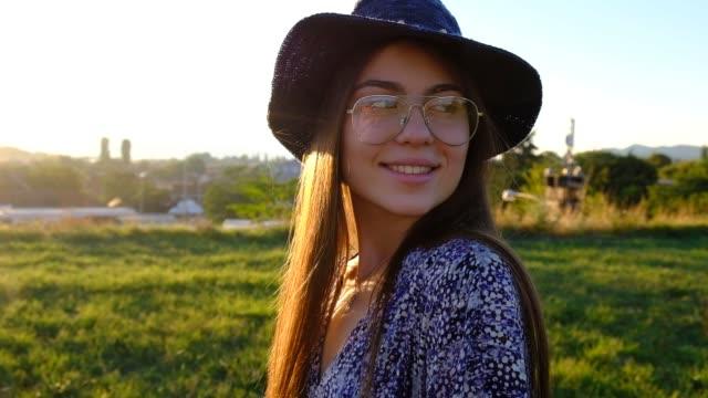 schöne weibliche teenager blickend und lächelnd in die kamera in zeitlupe - kopfbedeckung stock-videos und b-roll-filmmaterial