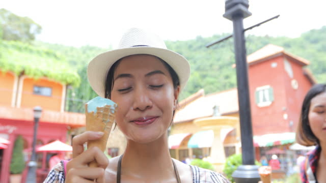 Beautiful female tourist wearing a hat and eating ice cream on summer holidays