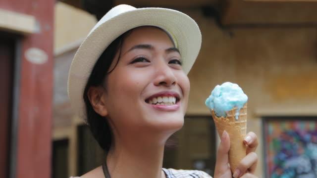 bir şapka giymiş ve yaz tatillerini üzerinde dondurma yemek güzel kadın turist - ice cream stok videoları ve detay görüntü çekimi