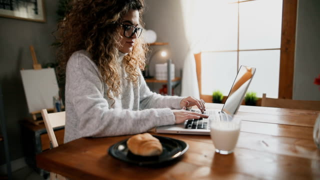 Beautiful female using laptop and having breakfast in the kitchen Beautiful female using laptop and having breakfast in the kitchen surfing the net stock videos & royalty-free footage