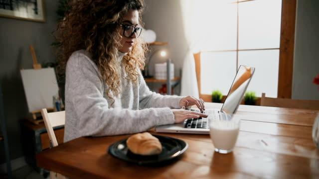 beautiful female using laptop and having breakfast in the kitchen - surfować po internecie filmów i materiałów b-roll