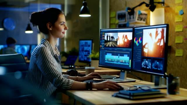 美しい女性のビデオ撮影は彼女のパソコンに映像を編集、彼女は夜、ドリンク コーヒー遅く創造的なオフィス空間で働いています。 - 編集者点の映像素材/bロール