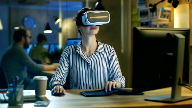 Beautiful Female Virtual Reality Engineer/ Developer Wearing VR Headset Creates Content. She Works in a Creative Designers Studio. video