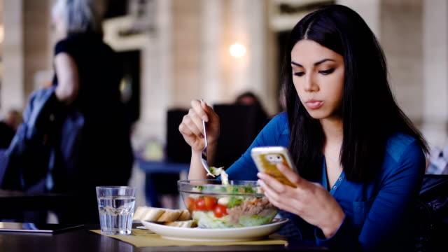 schöne philippinische frau essen einen salat und auf handy lesen - salat speisen stock-videos und b-roll-filmmaterial