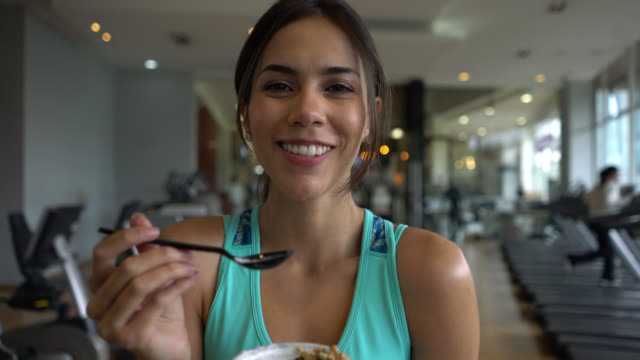 vídeos de stock, filmes e b-roll de lindo apto mulher na academia fazendo uma pausa para comer um parfait de enquanto enfrenta a câmera sorrindo - comendo