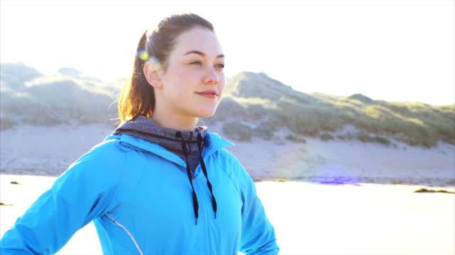 stockvideo's en b-roll-footage met mooie fit vrouw genieten van frisse lucht op strand na het uitvoeren van - handen op de heupen