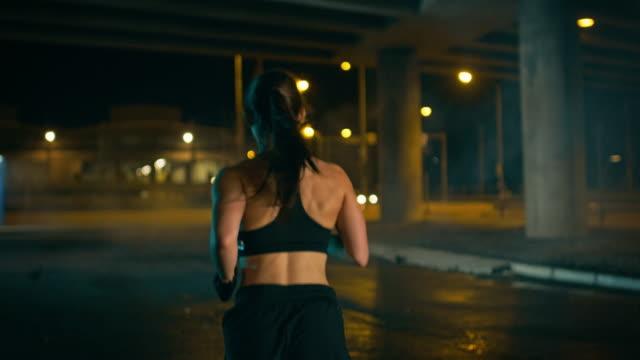 vidéos et rushes de belle fille de remise en forme athletic top noir et shorts est jogging dans la rue. elle est en train de faire une séance d'entraînement dans un environnement urbain sous pont un soir avec des voitures en arrière-plan. - joggeuse