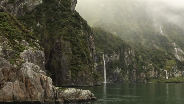 beautiful fjord milford sound waterfall tracking in distance - fiordo video stock e b–roll