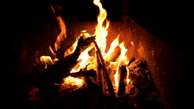 Beautiful flames from burning slices wood in mangal at night. Bonfire inside metal brazier at darkness. Firewood burns to preparation for cooking barbecue. Concept of warmth and rest. Top view