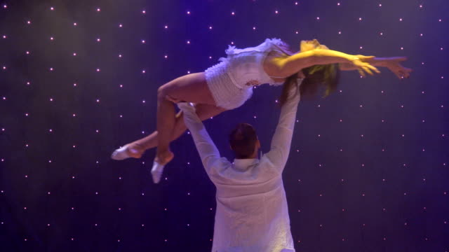 Beautiful flexible acrobats performs trick on stage in theatre Beautiful couple dances in duet on colorful stage in modern theatre. The acrobats performs beautiful tricks and gently moves and contacts with each other. musical theater stock videos & royalty-free footage