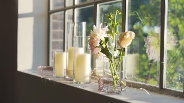 窓の棚の上に座って美しい花とキャンドル - ベンチ点の映像素材/bロール