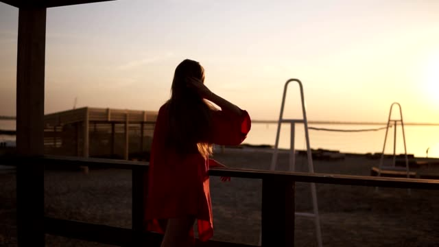 Beautiful footage of a morning sea or ocean sunrise. Attractive long haired blonde woman in red dress standing facing to the water video