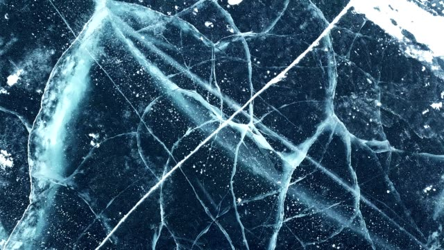 Beautiful footage of cracks surface of the frozen lake of Baikal lake in winter season from drone.