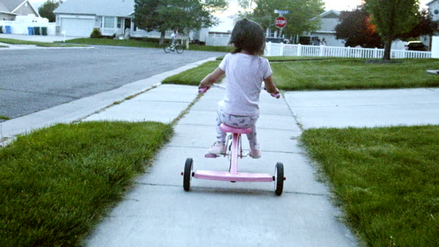 A Beautiful Four Year Old Girl Rides Her Tricycle Along a Sidewalk in a Nice American Middle Class Neighborhood in the Summer Time