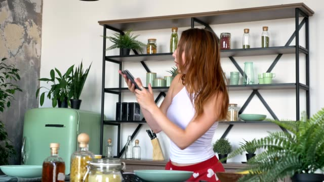 beautiful ginger woman texting on cell phone and dancing in modern kitchen, happy and joyful lady with perfect body - tułów filmów i materiałów b-roll