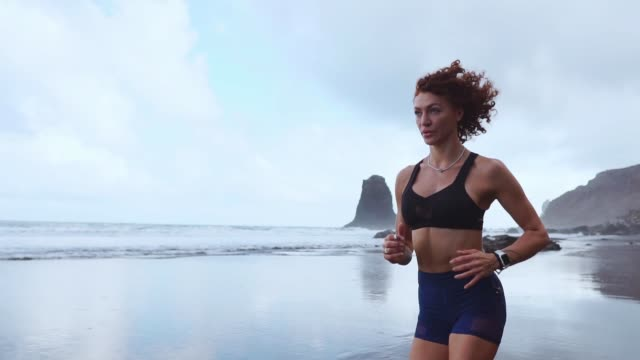 Beautiful girl athlete in sportswear runs along the shore of the Atlantic Ocean in the morning. The concept of a healthy lifestyle. Athletic physique
