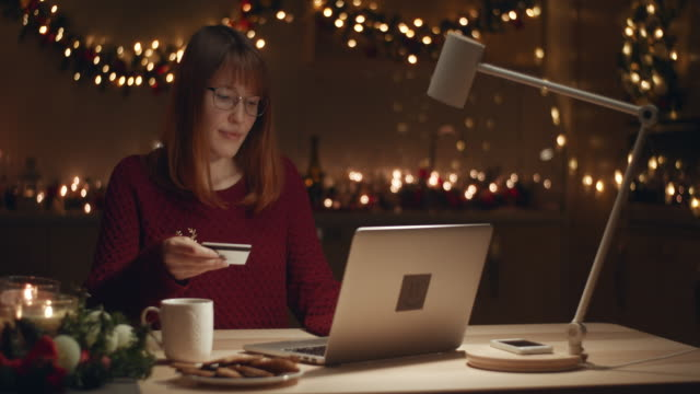 a beautiful girl buys herself a christmas gift through an online store. she pays by credit card online - treedeo christmas stock videos & royalty-free footage