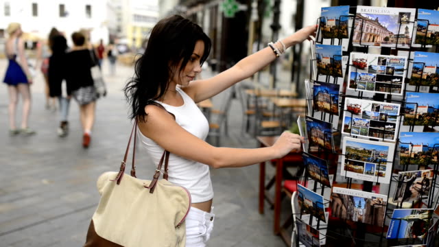 beautiful girl choosing from postcard stand on the street. - postcard 個影片檔及 b 捲影像
